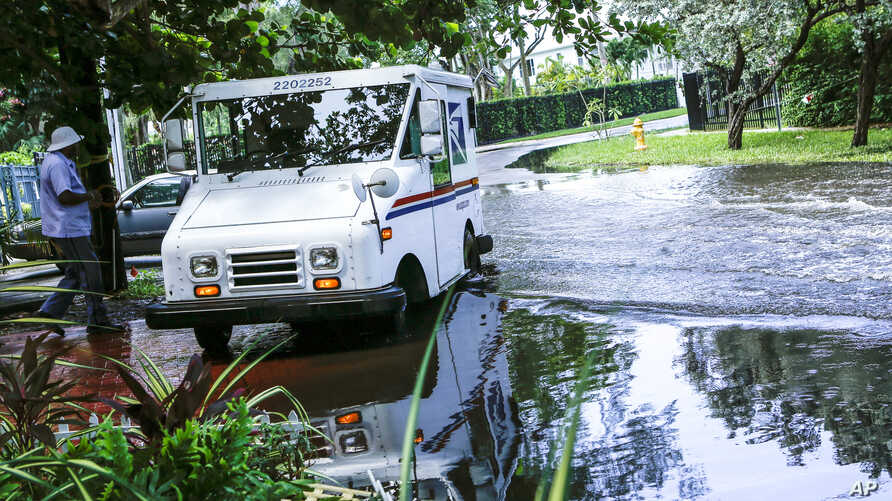 In this Wednesday, June 19, 2019 photo, a postal worker returns to their truck parked on a flooded street a few miles from the…