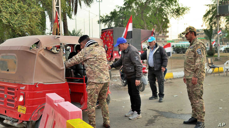 Iraqi security forces and members of Saraya Salam (Peace Brigades) militia search people heading to Tahrir Square where ongoing…