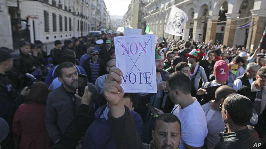 """An Algerian demonstrator holds a placard that reads """"no vote"""" during a protest against the government and the upcoming…"""