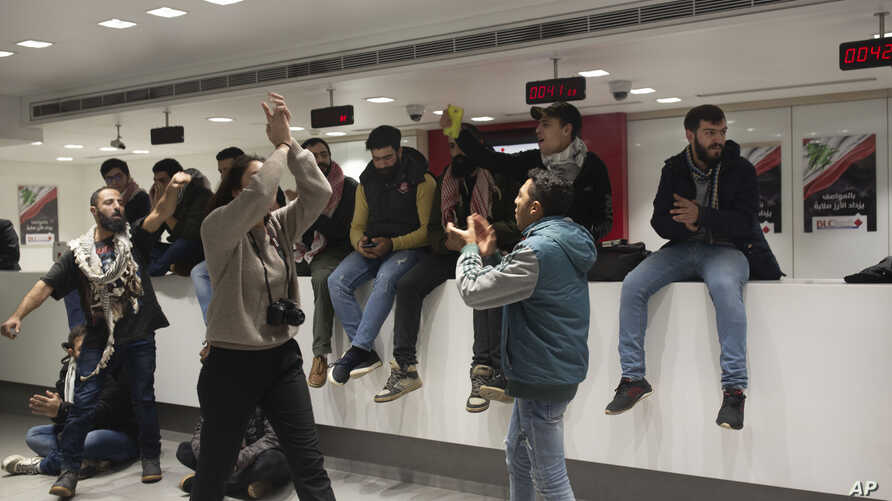 Anti-government protesters occupy the Hamra branch of BLC Bank Dec. 28, 2019 in Beirut, Lebanon. Banks have imposed weekly…