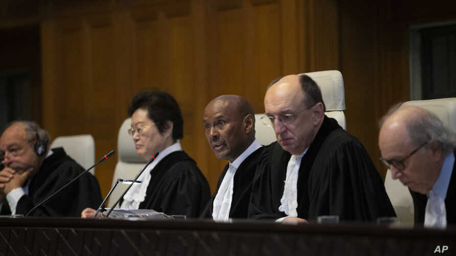 Presiding judge Abdulqawi Ahmed Yusuf of Somalia, center, and other judges open the first day of three days of hearings in the…