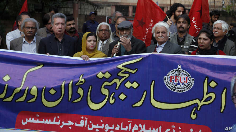 """Pakistani journalists and rights activists hold a banner reading as """"Solidarity with Dawn Workers"""" during a demonstration in…"""