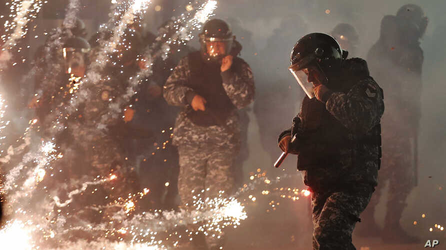 Lebanese riot policemen run from firecrackers that fired by the supporters of the Shiite Hezbollah and Amal Movement groups, as…
