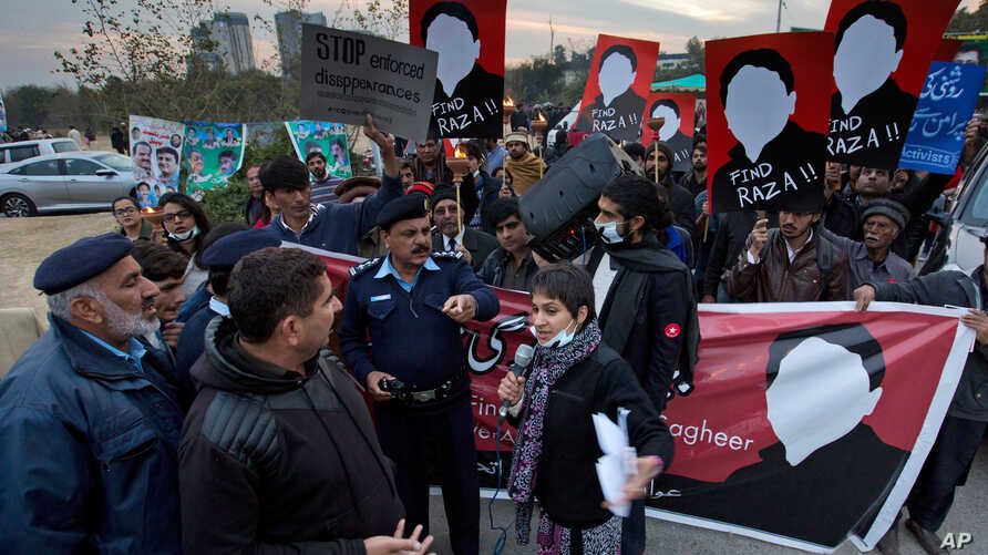 FILE - In this Jan. 11, 2018 file photo, Pakistani human rights activists talk to police officers during a rally against…
