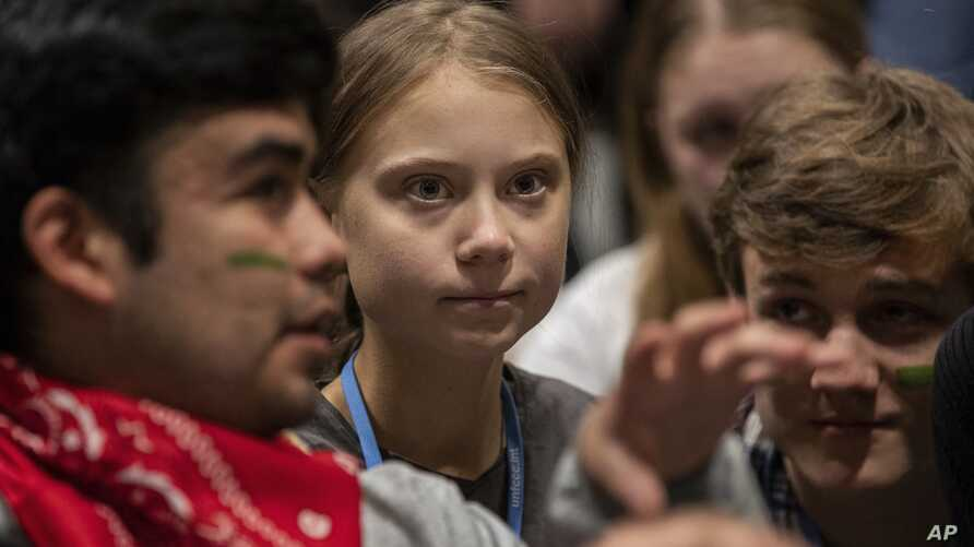 Climate activist Greta Thunberg, center, talks with other climate activists youth at the COP25 climate talks summit in Madrid,…