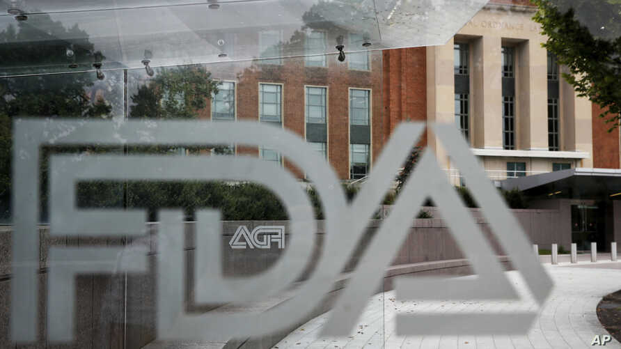 FILE - This Aug. 2, 2018, file photo shows the U.S. Food and Drug Administration building behind FDA logos at a bus stop on the…