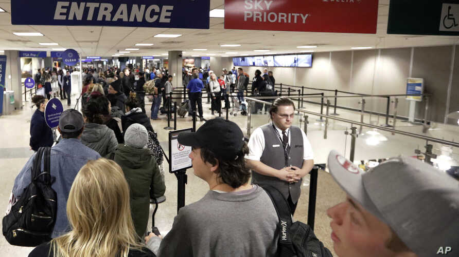 FILE - In this Wednesday, Nov. 27, 2019, file photo, travelers walk through a security checkpoint in Terminal 2 at Salt Lake…