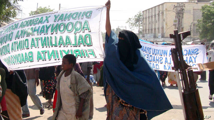 "Protesters carry banners which reads"" Down with those who carried the killings"" in Mogadishu, Somalia, Monday, Dec. 7, 2009. …"