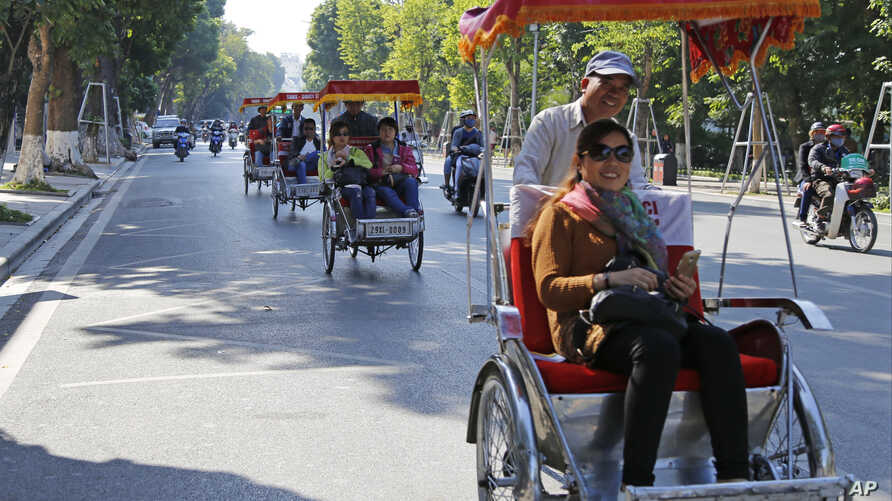 Chinese tourists ride rickshaws for sightseeing in Hanoi, Vietnam, Thursday, Dec. 1, 2016. China tops the list of number of…