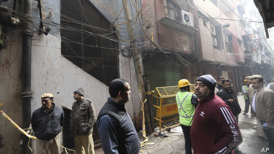 Policemen and neighbors stand in front of an ill-fated building which caught fire on Sunday, in New Delhi, India, Monday, Dec…