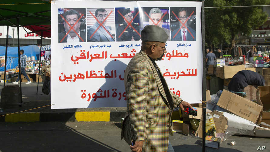 """A protester walks past a poster with defaced pictures of Iraqi politicians and Arabic that reads """"wanted by the Iraqi people…"""