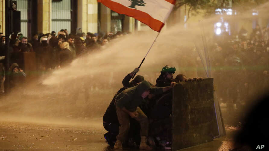 Anti-government protesters wave a Lebanese flag and hide behind a wood barrier from a water cannon as they clash with the riot…