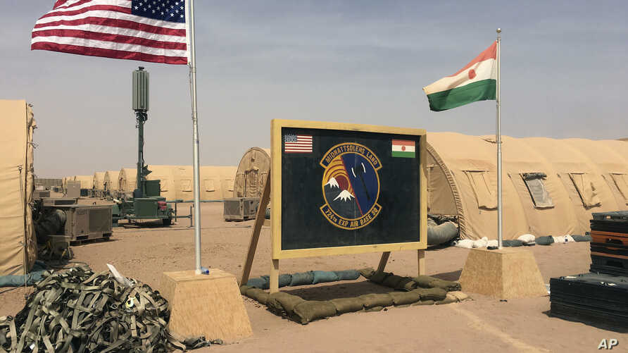 In this photo taken Monday, April 16, 2018, a U.S. and Niger flag are raised side by side at the base camp for air forces and…