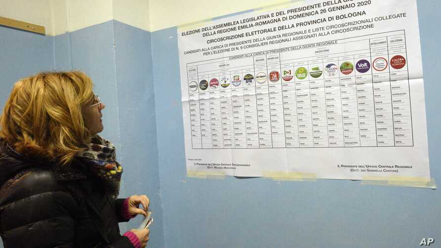 A woman looks at a candidates' list for Emilia Romagna region elections, at a polling station in Bologna, Italy, Sunday, Jan…