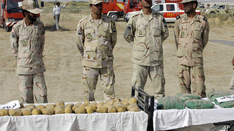 Iranian police officers stand behind narcotic drugs  which were seized at border of Iran and Afghanistan, a known drug…