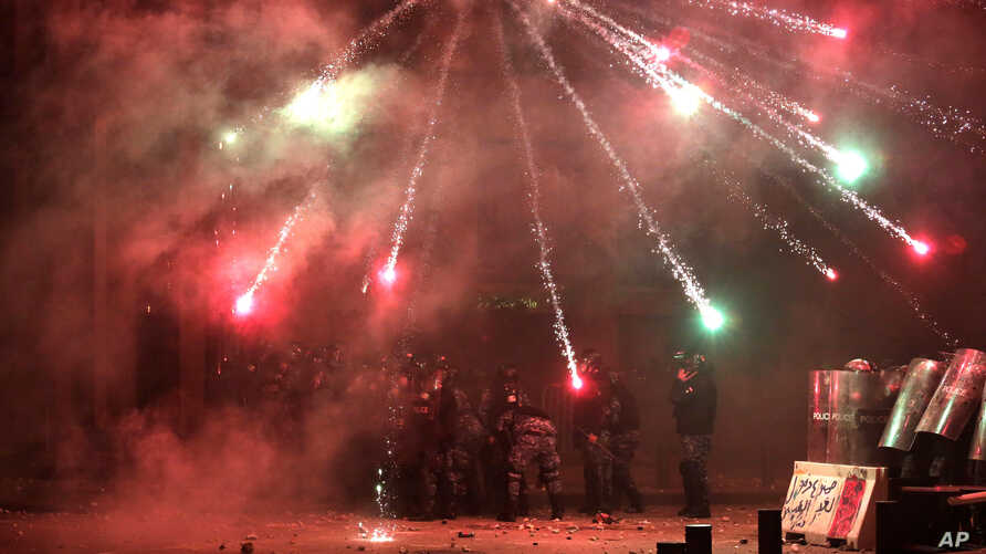 Anti-government protesters use fireworks against Lebanese riot police during a protest at a road leading to the parliament…