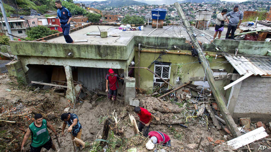 Locals work to clean up mud and debris around houses destroyed by a landslide after heavy rains in Vila Ideal neighborhood,…