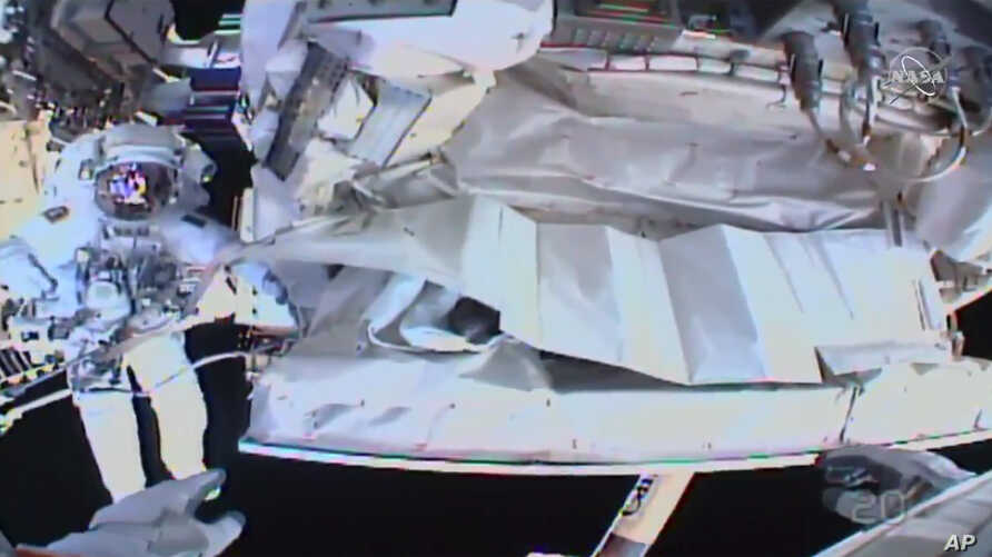 This photo provided by NASA shows the view from NASA's Andrew Morgan's helmet cam as Italian astronaut Luca Parmitano works…