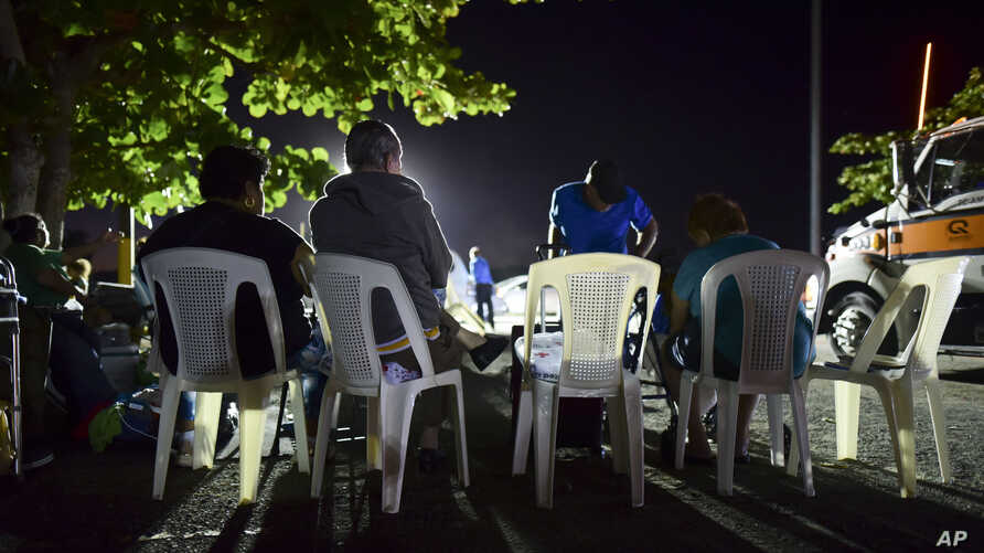 Neighbors remain outdoors using camping tents and portable lights for fear of possible aftershocks on their first night after a…