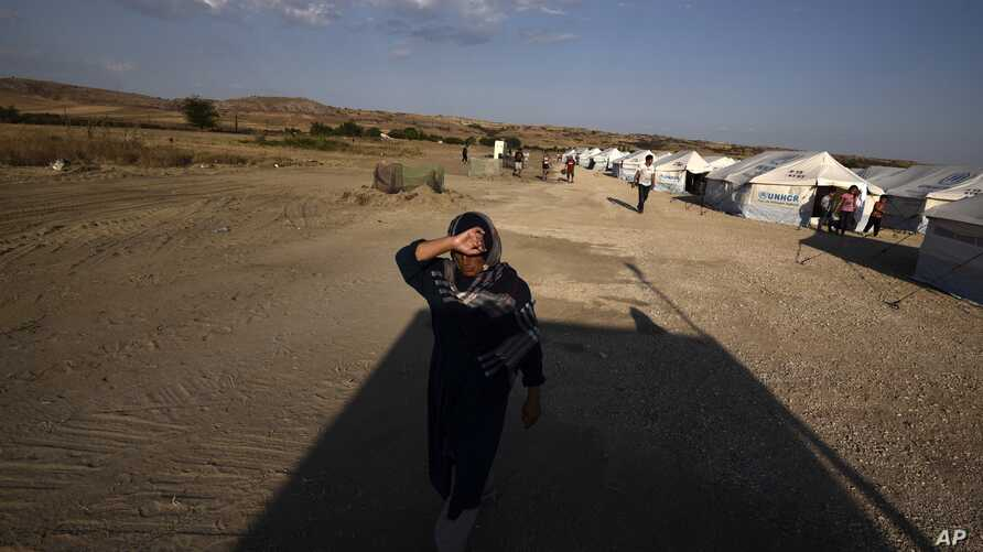 A woman walks at a refugee camp in Nea Kavala, northern Greece, Tuesday, Sept. 3, 2019. About 1,500 asylum-seekers transported…