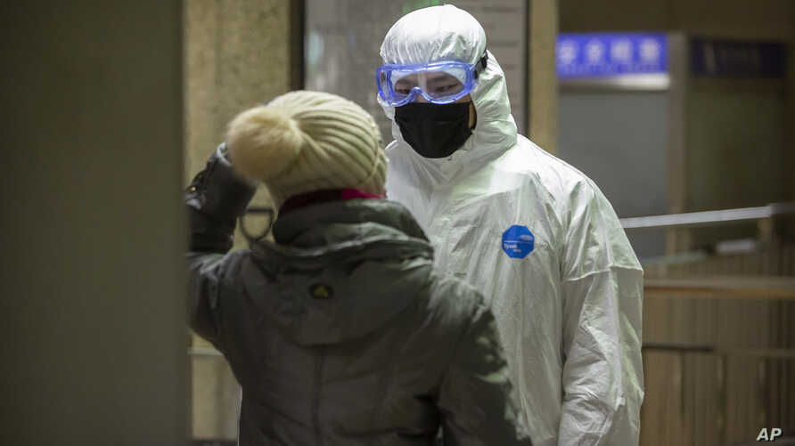 A worker wearing a hazardous materials suit checks a passenger at a subway station in Beijing, Friday, Jan. 24, 2020. China…