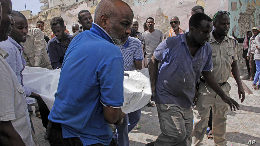 People remove a dead body after a vehicle bomb attack on a security checkpoint located near the presidential palace, in…