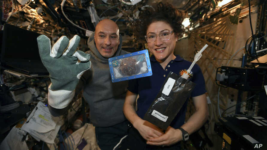 In this photo made available by U.S. astronaut Christina Koch via Twitter on Dec. 26, 2019, she and Italian astronaut Luca…
