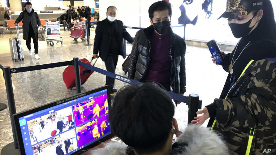 Travelers pass through a health screening checkpoint at Wuhan Tianhe International Airport in Wuhan in southern China's Hubei…