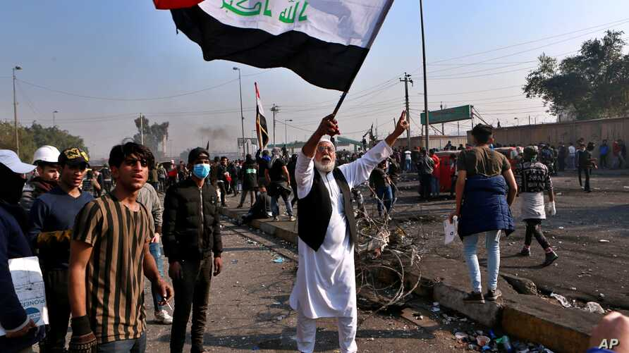 A protester waves the national flag during clashes with security forces in central Baghdad, Iraq, Monday, Jan. 20, 2020. Iraqi…