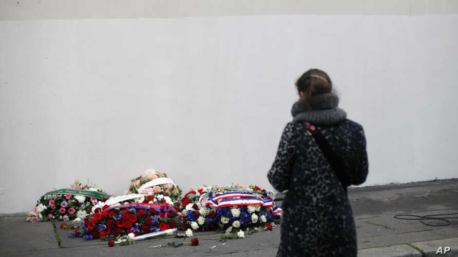 A woman pays tribute in front of a wreath of flowers, outside the satirical newspaper Charlie Hebdo's former office, after a…