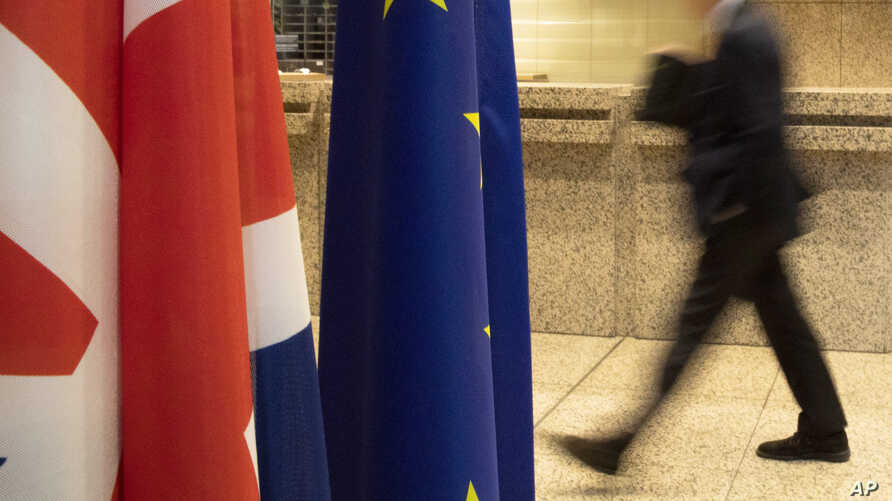 A man walks by the Union Flag and the EU flag inside the European Council building in Brussels, Monday, Jan. 27, 2020. The U.K…