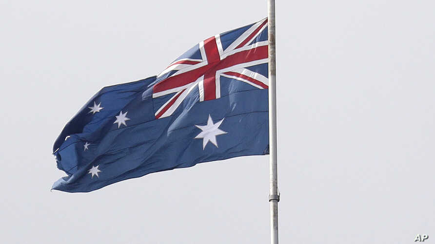 People climbing the Sydney Harbour Bridge stop under a flag flying at half-mast as mark of mourning and respect in Sydney…