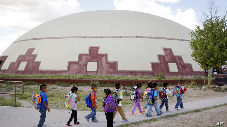 FILE - In this Sept. 25, 2014 file photo, students walk between buildings at the Little Singer Community School in Birdsprings,…