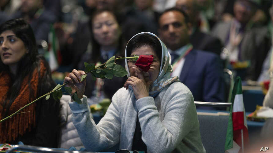 One of the Iranian Americans supporting the National Council of Resistance of Iran holds a single rose