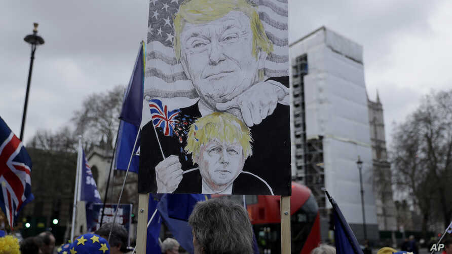 Remain in the European Union, anti-Brexit protesters, including one with a placard depicting British Prime Minister Boris…