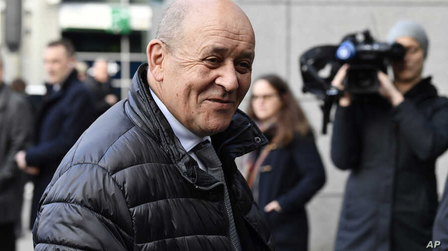 French Foreign Minister Jean-Yves Le Drian speaks with journalists as he arrives for a meeting to discuss the situation in…