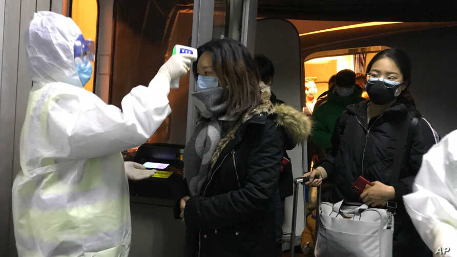 Health Officials in hazmat suits check body temperatures of passengers arriving from the city of Wuhan Wednesday, Jan. 22, 2020…