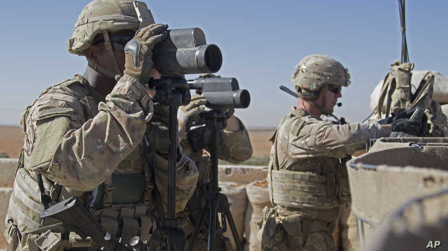 In this Nov. 1, 2018, photo released by the U.S. Army, soldiers surveil the area during a combined joint patrol in Manbij,…
