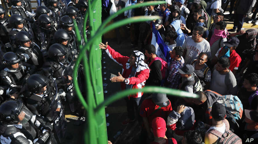Migrants plea to Mexican National Guardsmen at the border crossing between Guatemala and Mexico in Tecun Uman, Guatemala,…
