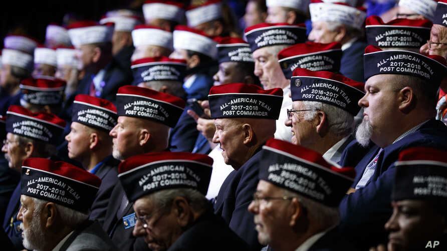 Audience members listen as President Donald Trump speaks during the Veterans of Foreign Wars of the United States National…