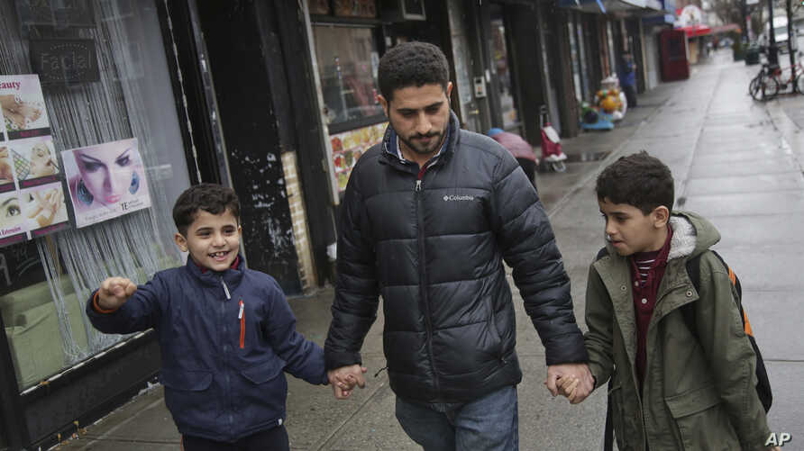 In this March 21, 2019, photo, Sadek Ahmed walks with his sons Adel, 9, right, and Mutaz, 7, after picking them up from school…