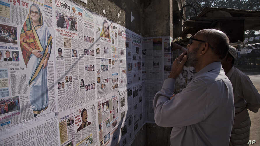 Bangladeshis read newspapers pasted on a wall in Dhaka, Bangladesh, Monday, Dec. 31, 2018. Bangladesh's ruling alliance won…