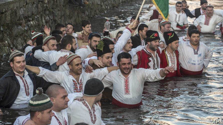 Bulgarians sing and chain dance in the icy waters of the Tundzha river during Epiphany, in Kalofer, Bulgaria, Monday, Jan. 6,…