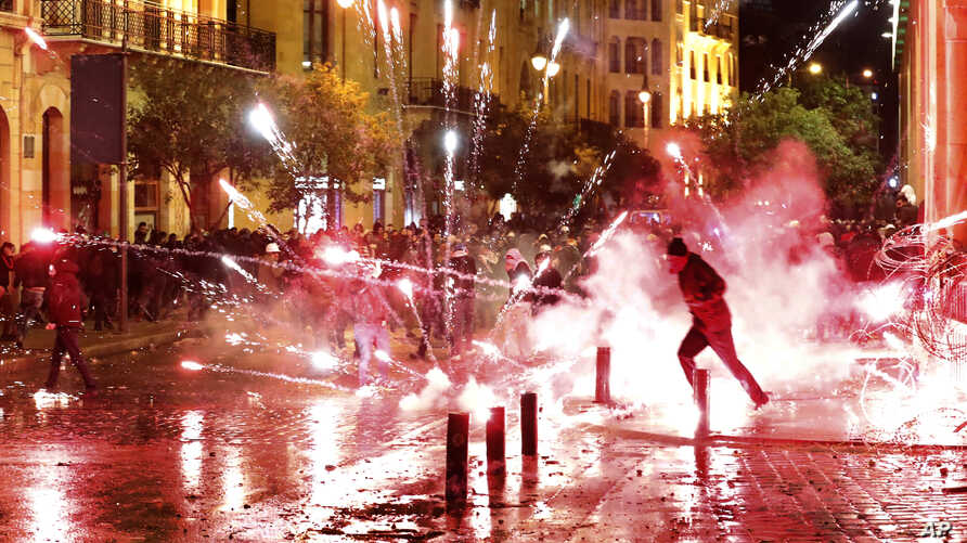 Anti-government protesters throw firecrackers at riot police during a demonstration against the new government, near Parliament…