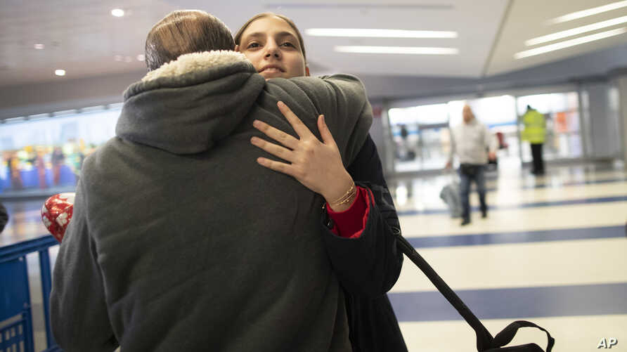 In this Dec. 3, 2019, photo, Mohammed Hafar hugs his daughter Jana after she arrives at JFK Airport in New York. Jana had been…