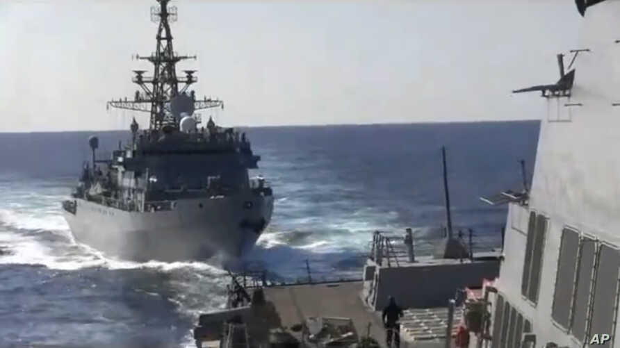 This photo provided bythe U.S. 5th Fleet, shows a Russian Navy ship approaching an American warship in the North Arabian Sea,…