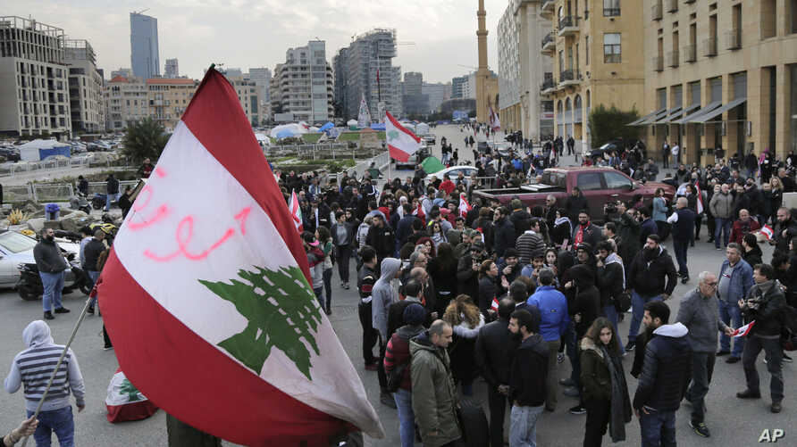 Anti-government protesters block a road that links to the Martyrs square where they set their protest encampment, after it was…