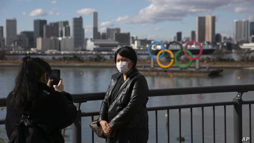 A tourist wearing a mask pauses for photos with the Olympic rings in the background Wednesday, Jan. 29, 2020, in the Odaiba…