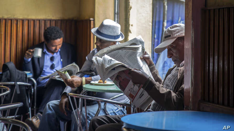 FILE - In this Monday, Oct. 10, 2016 file photo, Ethiopian men read newspapers and drink coffee at a cafe during a declared…