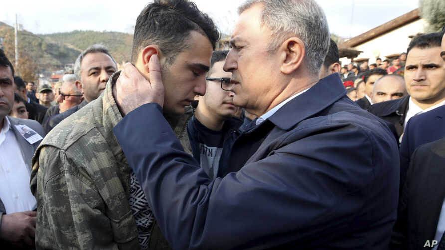 Turkey's Defence Minister Hulusi Akar speaks with brother of Halil Ibrahim Akkaya, no name available, one of Turkish soldiers…